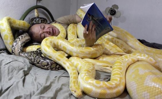 Мужчина в кровати с большой змеёй