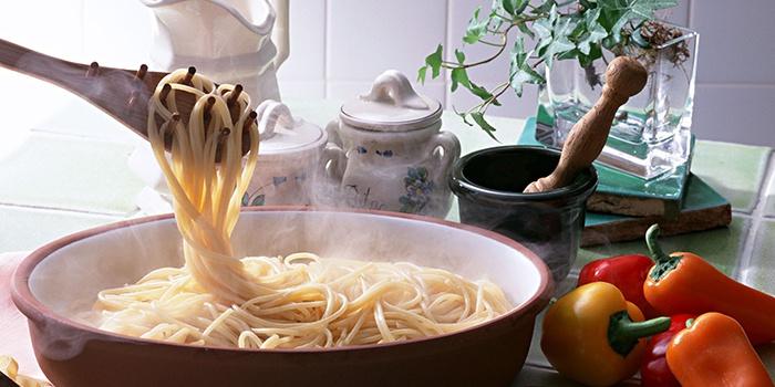 На кухонные щипцы наматывают спагетти