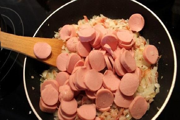Нарезанные сосиски в сковороде