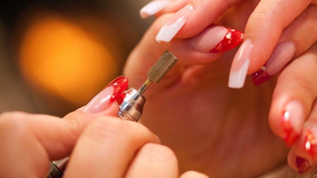 Обработка ногтей на женской руке аппаратом