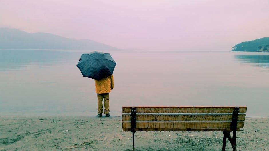Одинокий человек с зонтом у водоёма