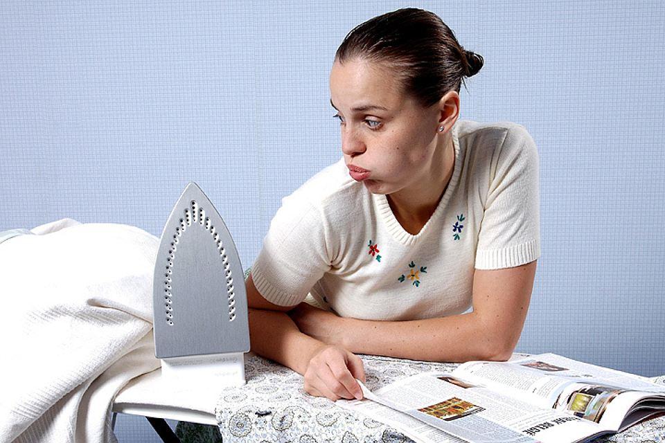Жещина читает журнал на гладильной доске с утюгом