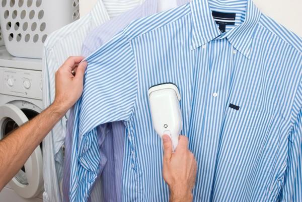 Отпаривателем гладят голубую рубашку с длинным рукавом