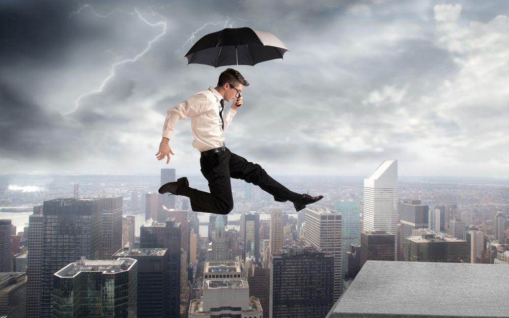 Парень летит над городом с помощью зонта