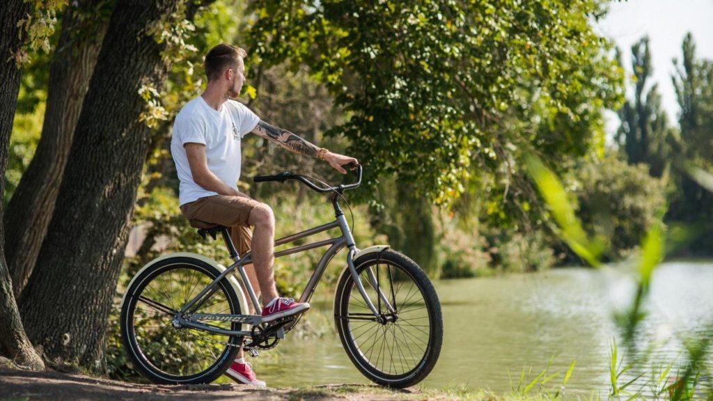 Парень с велосипедом на берегу реки