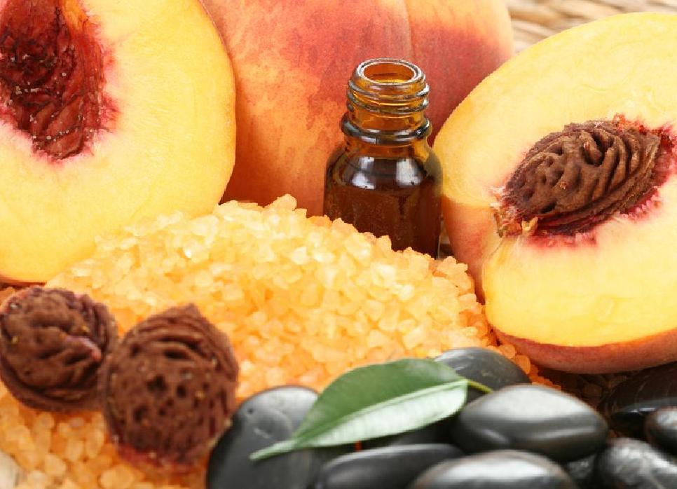Персиковое масло в бутылочке на фоне персиков