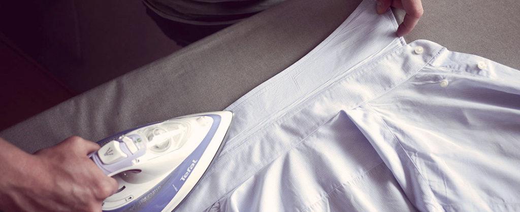 Человек гладит воротник рубашки