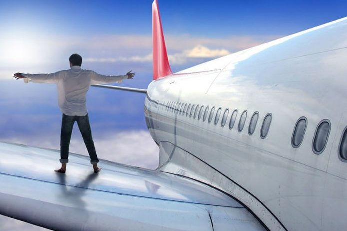 Мужчина стоит на крыле самолёта