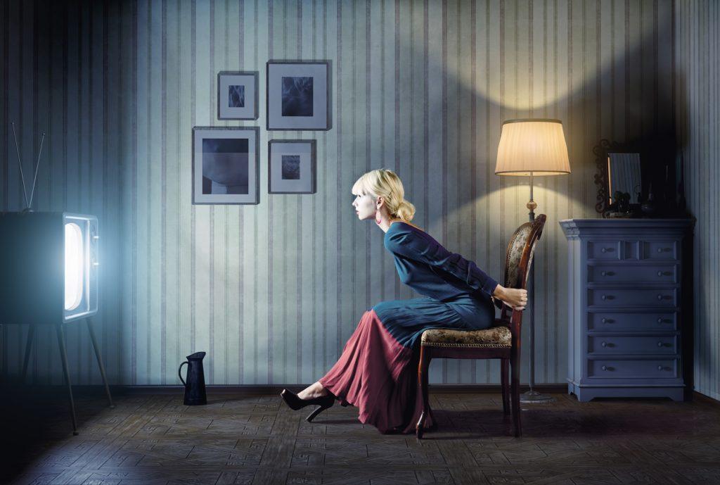 Женщина смотрит телевизор с близкого расстояния