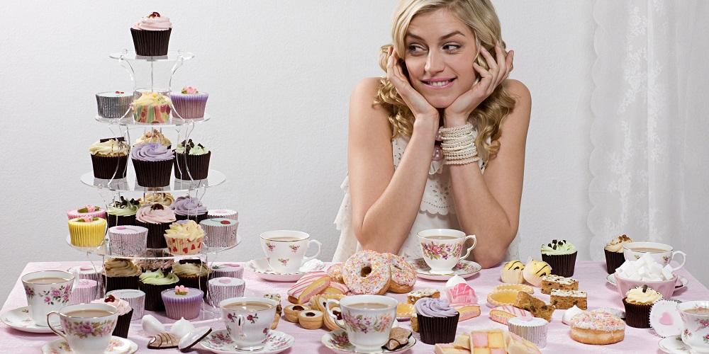Радостная девушка за столом с пирожными