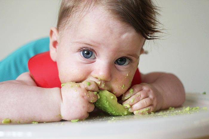 Ребёнок ест авокадо