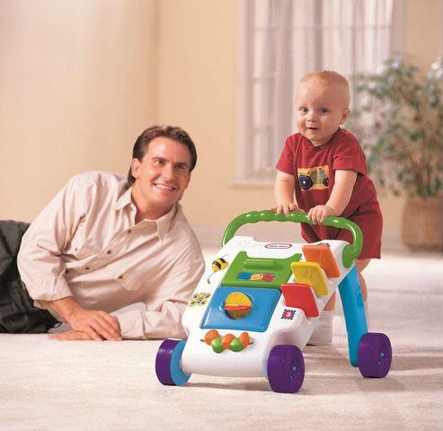 Ребёнок катит ходунки-каталку, папа слева смотрит и улыбается