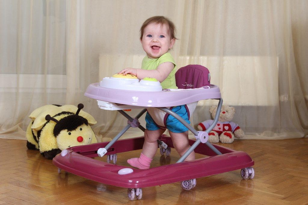 Ребёнок в ходунках с фиолетовой прямоугольной рамой