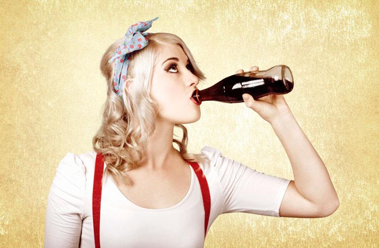 Девушка пьёт газировку