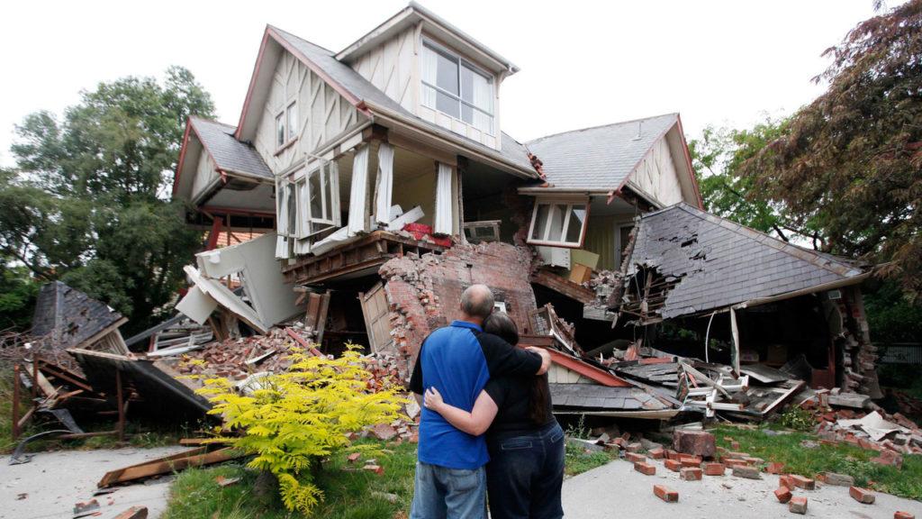 Семейная пара перед рухнувшим домом
