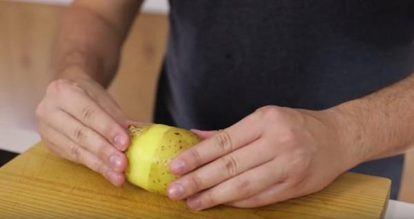 Снимают шкурку руками с картофелины, лежащей на деревянной доске