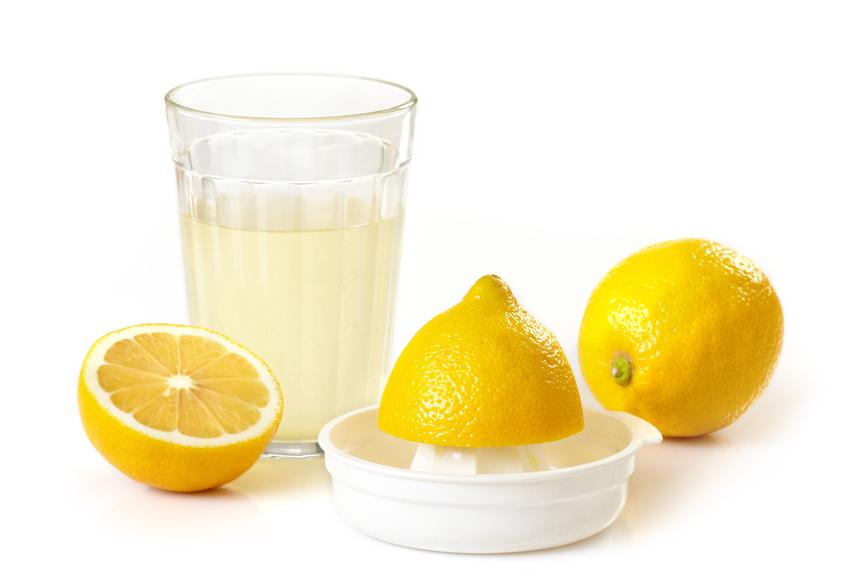 Сок лимона в прозрачном стакане и плоды одноимённого растения на столе