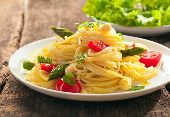 Спагетти с помидорами и зеленью на тарелке
