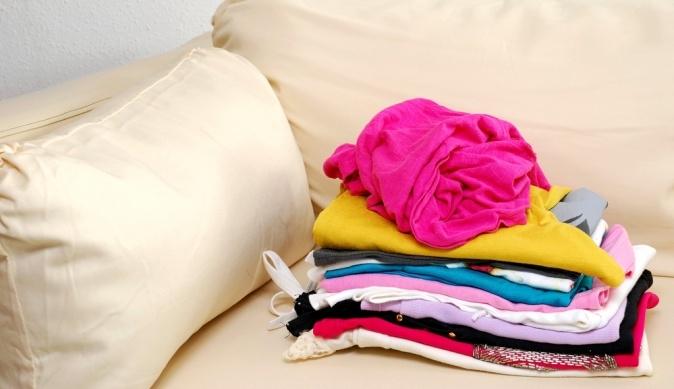 Стопка одежды со скомканной розовой вещью наверху на светлом диване