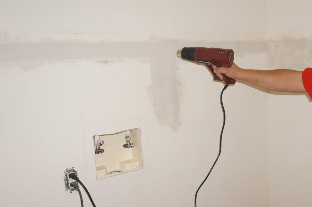 Строительным феном сушат стену