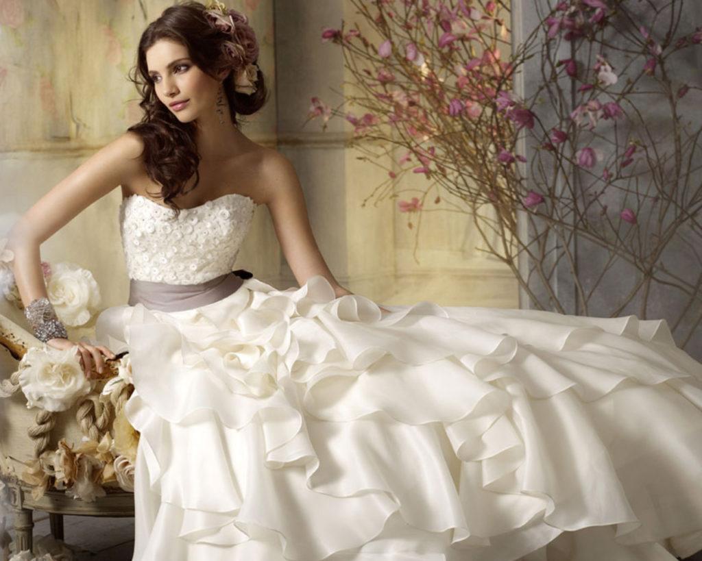 Девушка в свадебном платье сидит на красивой софе