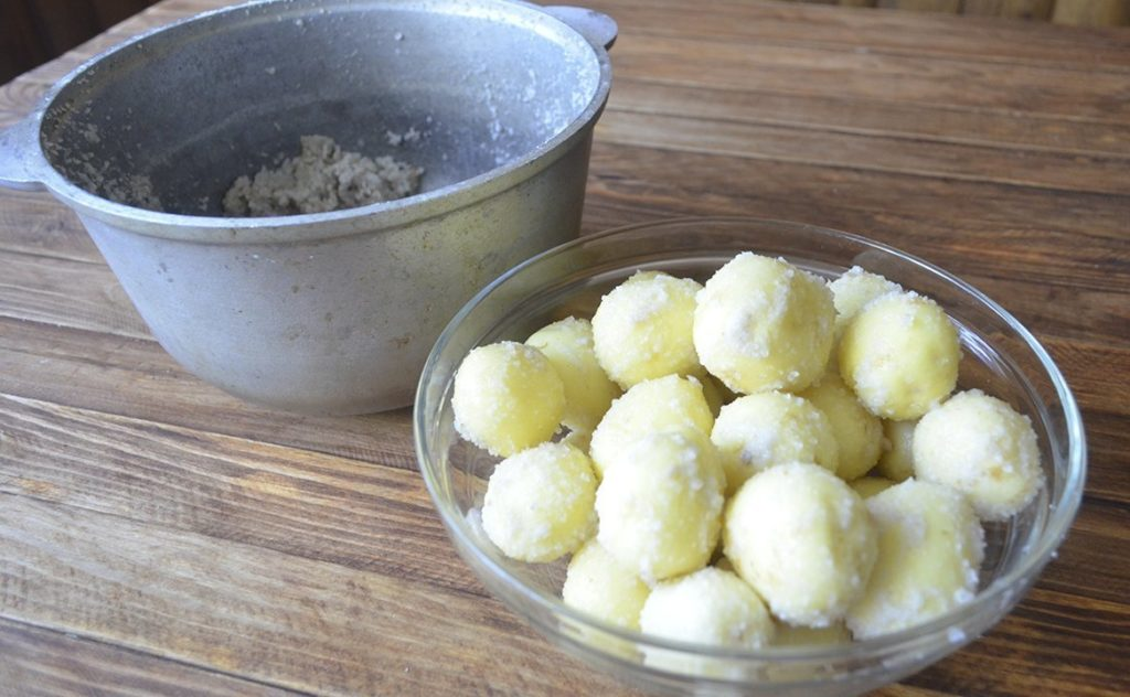 Сырой картофель в соли лежит в миске на столе