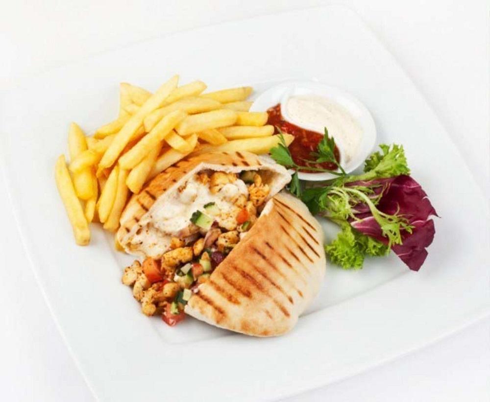 Тарелка с картошкой, овощами и шаурмой