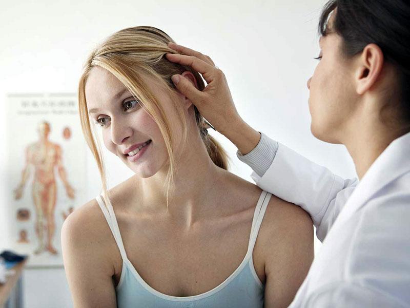 Трихолог осматривает волосы девушки