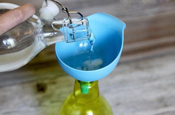 Уксус наливают через голубую воронку в жёлтую бутылку
