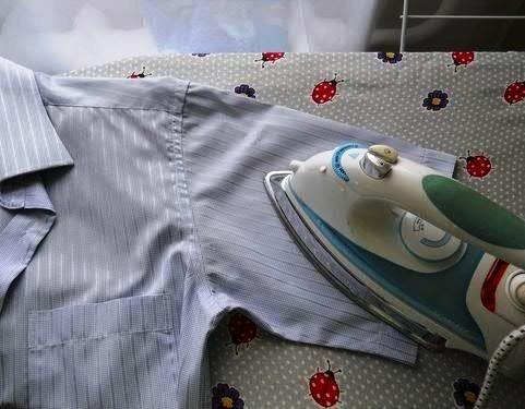Утюг на коротком рукаве мужской рубашки, разложенной на доске