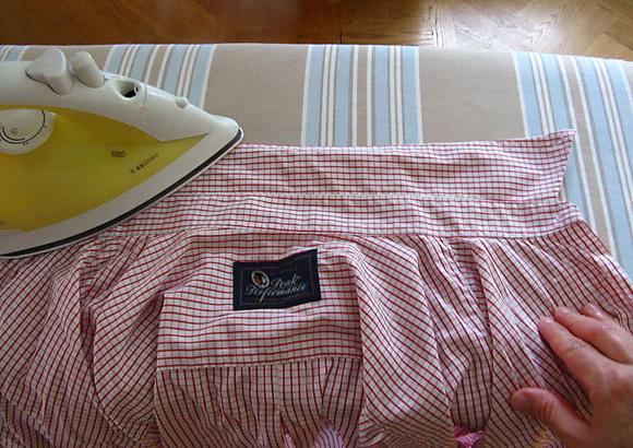 Утюг на воротнике белой рубашки в красную полоску