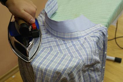 Утюгом правильно разглаживают кокетку рубашки в клетку