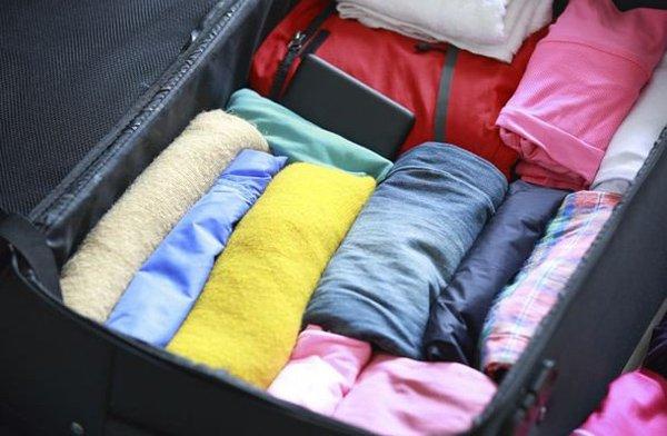 Вещи, сложенные валиками, в чемодане