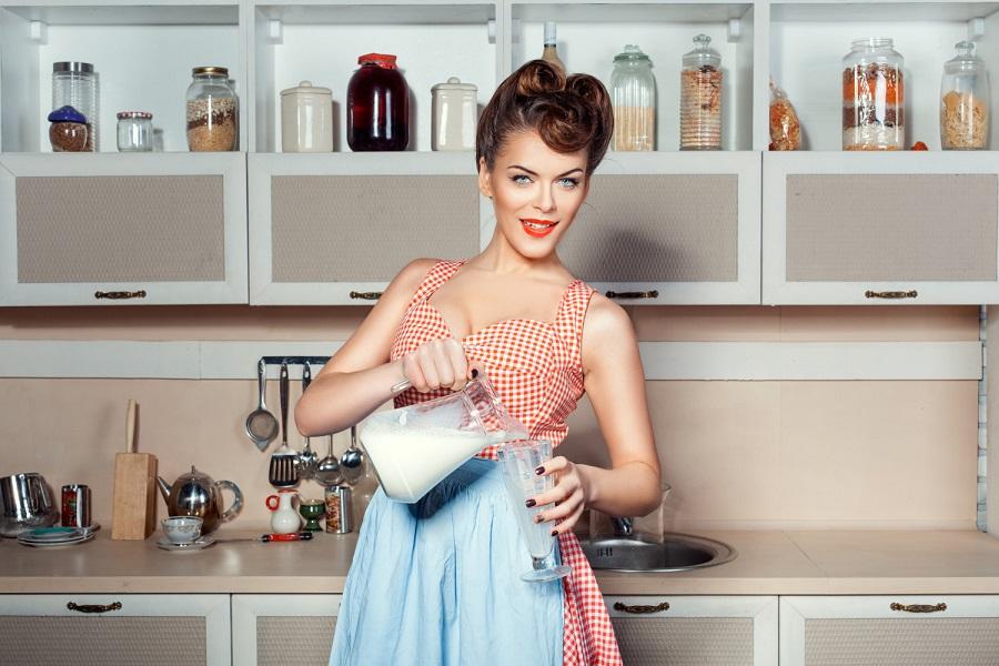 Женщина наливает молоко в стакан