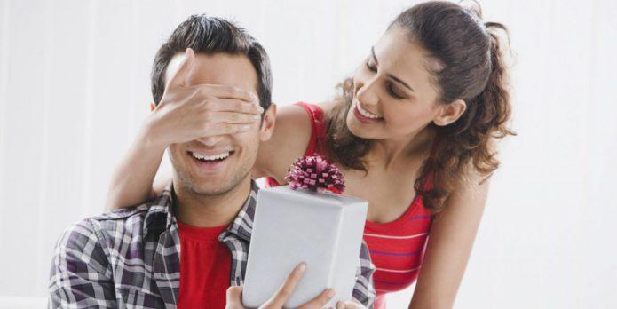 Женщина дарит мужчине подарок