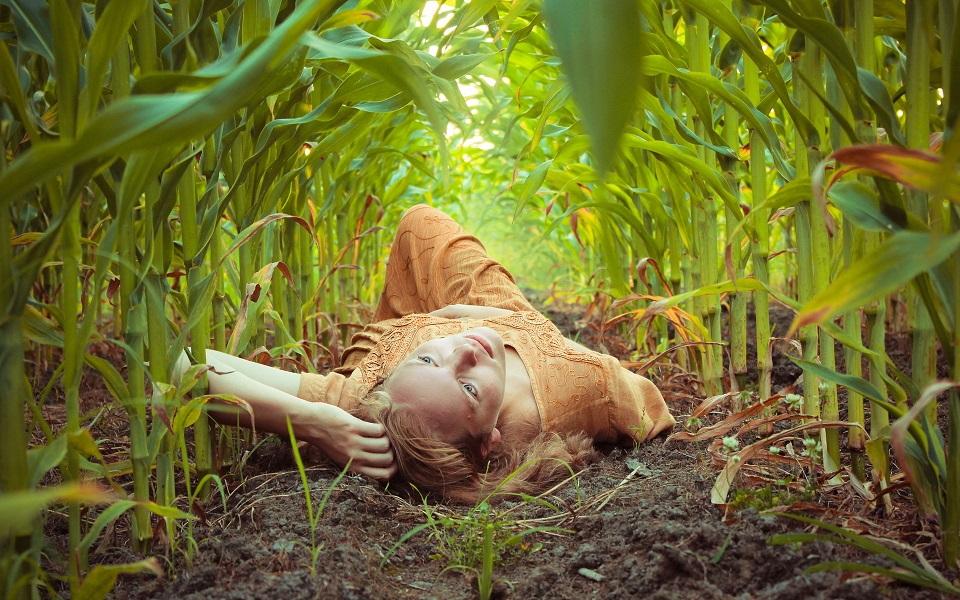 Женщина лежит на кукурузном поле