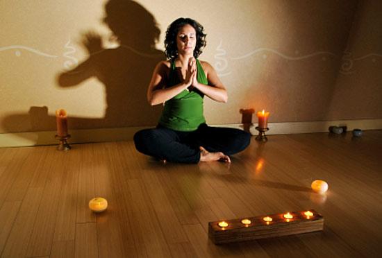 Женщина медитирует при свечах