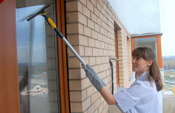 Женщина, моющая балконные окна стеклоочистителем