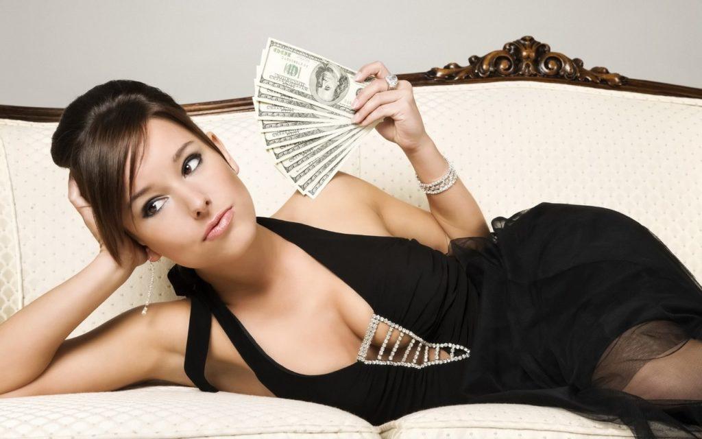 Женщина на диване держит деньги