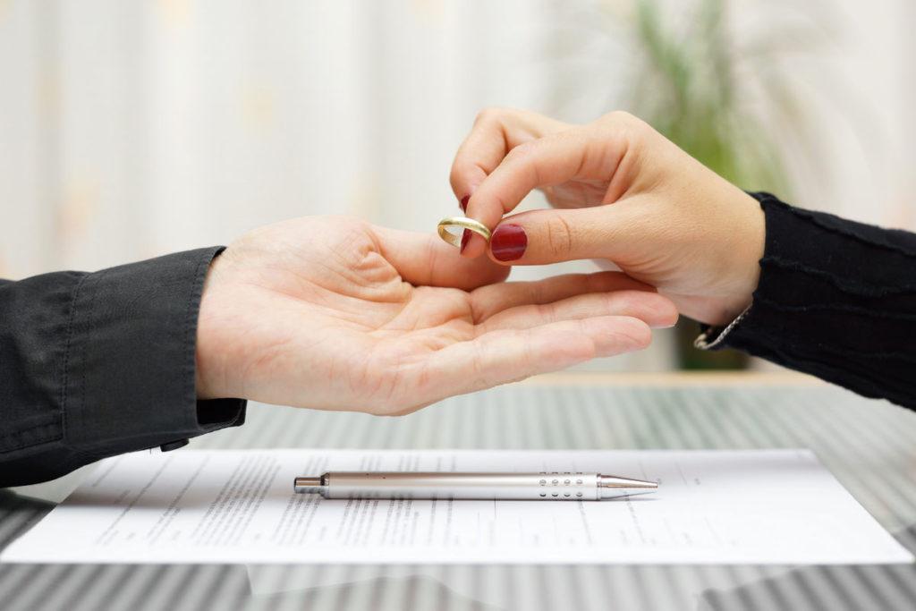 Женщина отдает супругу обручальное кольцо
