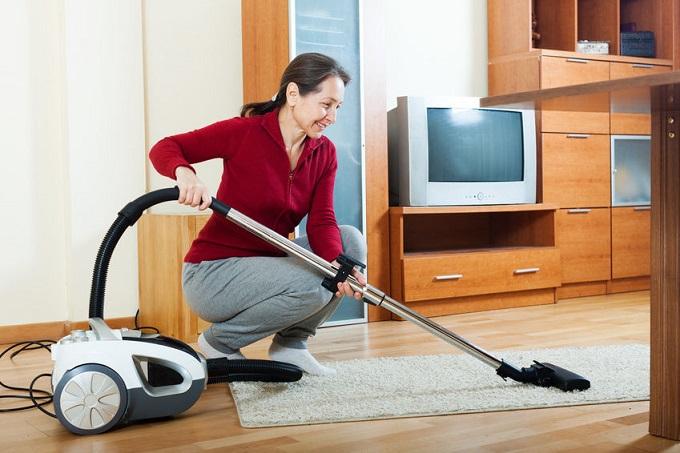 Женщина пылесосит ковёр