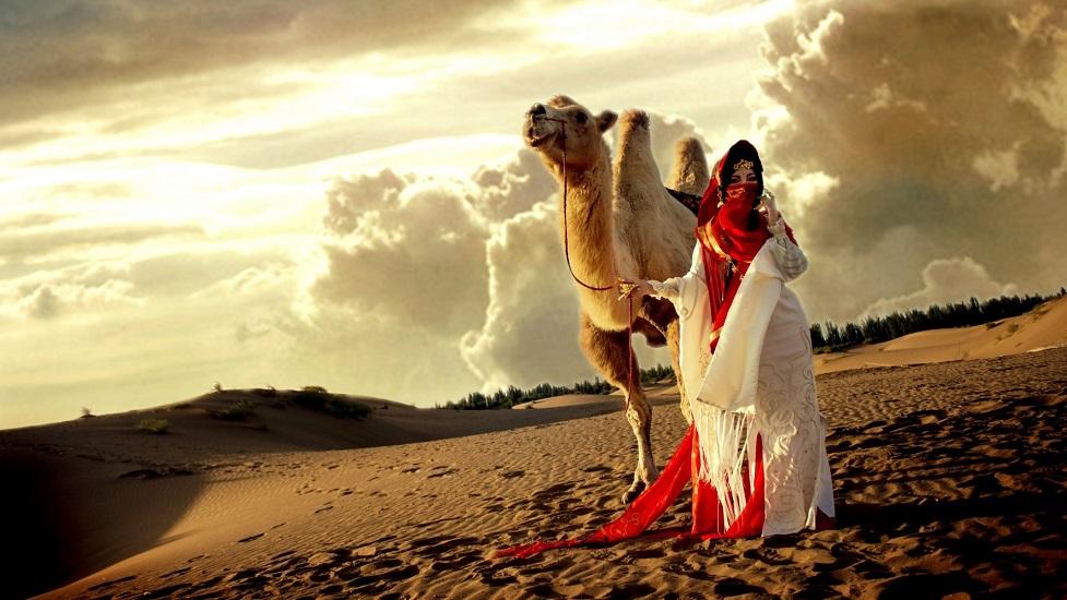 Женщина с верблюдом в пустыне
