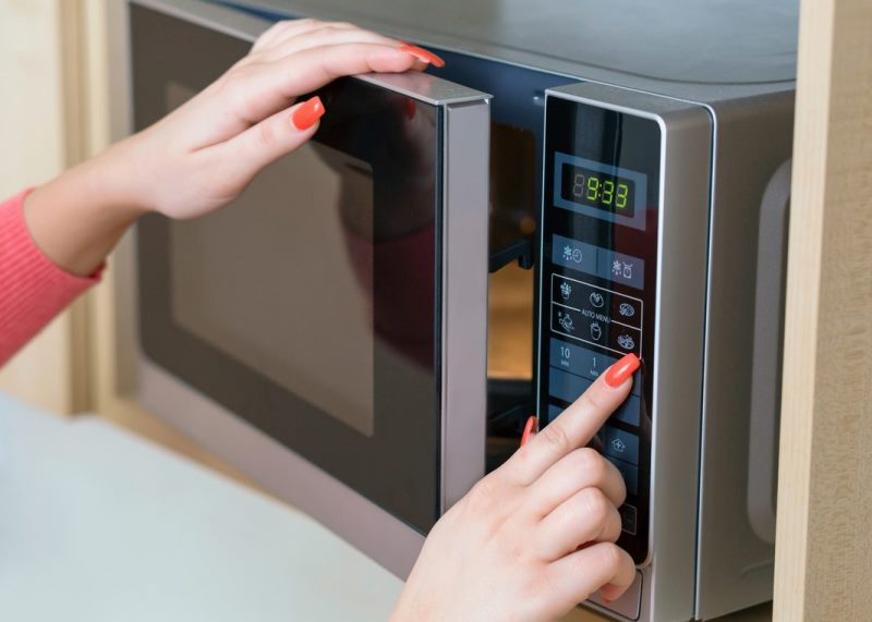 Женщина включает микроволновую печь