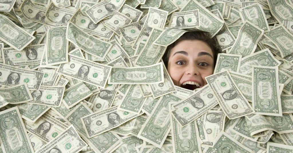 Женщина засыпана банкнотами